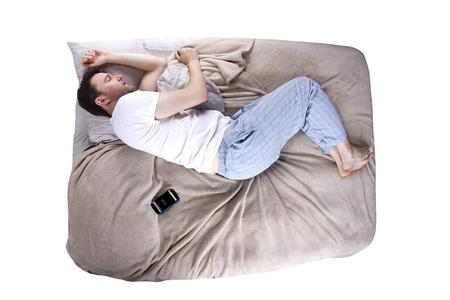 sleep: man snoozing modern cell phone alarm clock Stock Photo