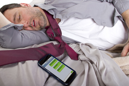 male sleeping in work clothes and receiving text messages from work