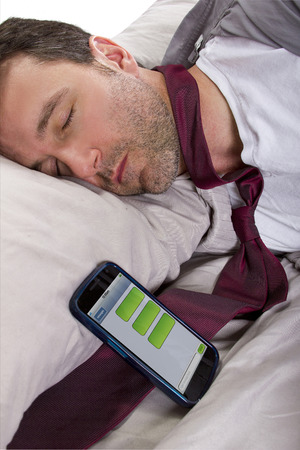 tardy: male sleeping in work clothes and receiving text messages from work