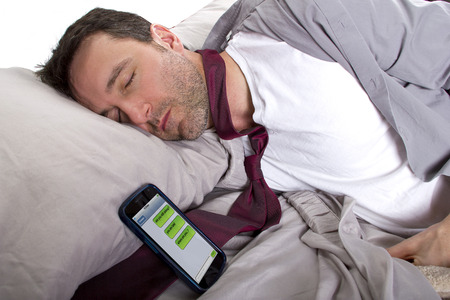 slacker: male sleeping in work clothes and receiving text messages from work