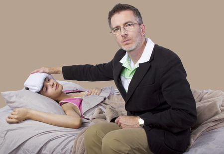 father taking care of teenager with cold or flu