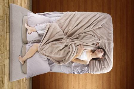Vista desde arriba de la hembra joven en la cama sin poder dormir Foto de archivo - 29300998