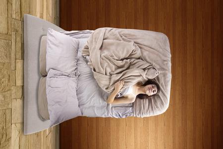 잠을 잘 수없는 침대에서 젊은 여성의 상위 뷰 스톡 콘텐츠 - 29301006