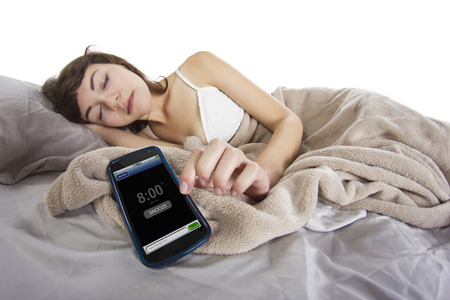 female snoozing modern cell phone alarm clock photo