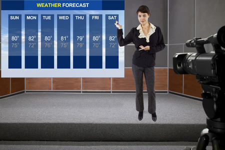 weather report: young woman on stage with weather chart and camera Stock Photo