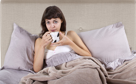 tomando refresco: joven cauc�sica tomando un caf� en la cama en la ma�ana