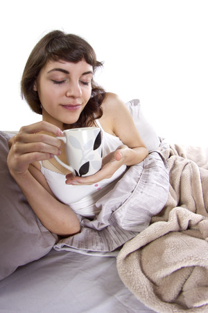 young caucasian woman having coffee in bed in the morning photo