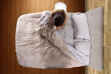 top view of young woman praying in the bedroom