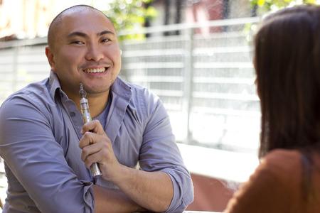 male smoker on a date using modern e-cigarette vaporizer