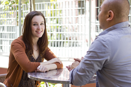 first date: interracial couple meeting on a casual first date outdoors