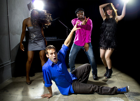 Caucasian man falls but confidently plays cool in a dance club Stock Photo
