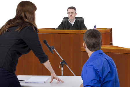 defendant: defendant with lawyer speaking to a judge in the courtroom
