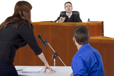 tax evasion: defendant with lawyer speaking to a judge in the courtroom