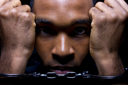 arrested criminal: close up portrait of hand cuffed black man