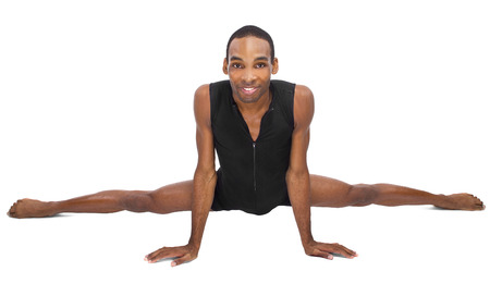 male ballet dancer warming up and showing flexibility on white background