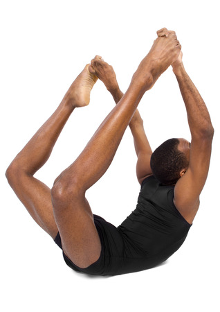 sitting on the ground: male ballet dancer warming up and showing flexibility on white background