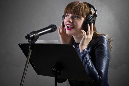stylish female singer with microphone and reading lyrics Stock Photo