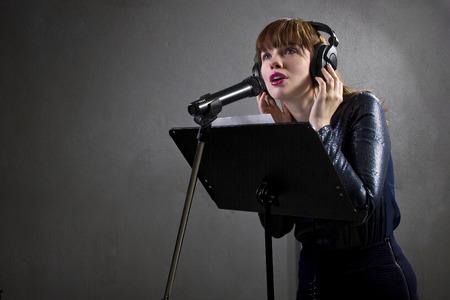 スタイリッシュな女性歌手マイクと歌詞を読んで 写真素材 - 33500372