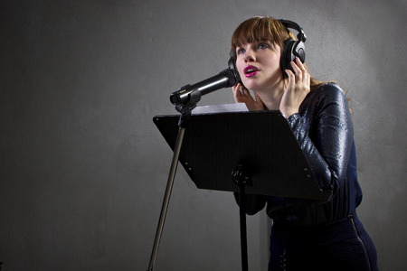 stylish female singer with microphone and reading lyrics Stock Photo