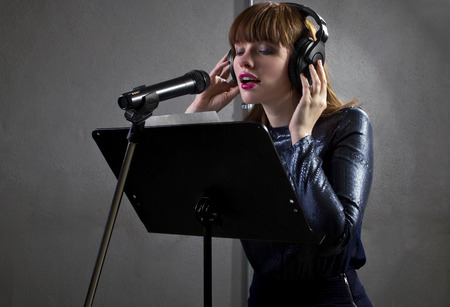 stylish female singer with microphone and reading lyrics Archivio Fotografico