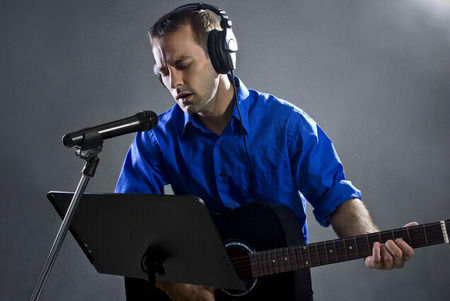 country music: male singer holding a guitar and wearing headphones on concrete background