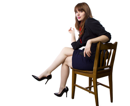 female executive sitting on a chair showing legs and heels on white background Stock fotó