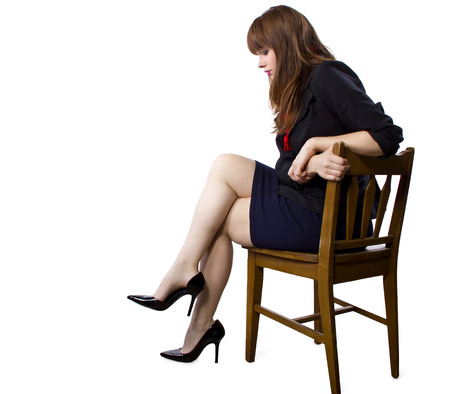 female executive sitting on a chair showing legs and heels on white background 版權商用圖片