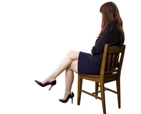 stool: female executive sitting on a chair showing legs and heels on white background Stock Photo