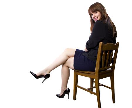 白い背景の上の脚とハイヒールを見せて椅子に座って女性エグゼクティブ 写真素材