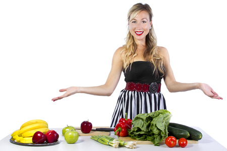 young caucasian female looking at fruits and vegetables on a table photo