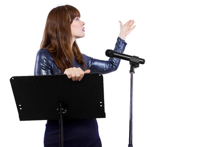 girl in shiny dress speaking on a microphone in a podium on white background