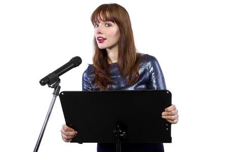 Chica en vestido brillante hablando en un micrófono en un podio en el fondo blanco Foto de archivo - 33948836