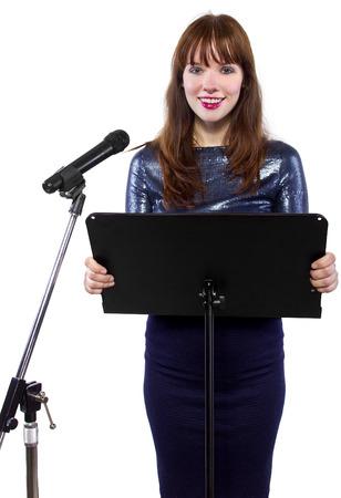 meisje in glanzende jurk spreken over een microfoon op een podium op witte achtergrond Stockfoto