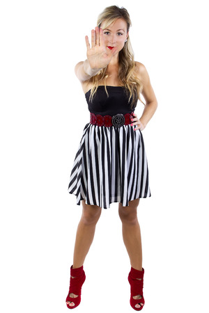 no heels: young caucasian female in striped dress with stop hand gesture on white background Stock Photo