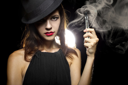 woman smoking or vaping an electronic cigarette to quit tobacco 写真素材