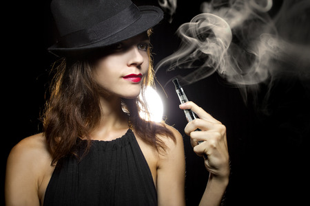 woman smoking or vaping an electronic cigarette to quit tobacco Standard-Bild