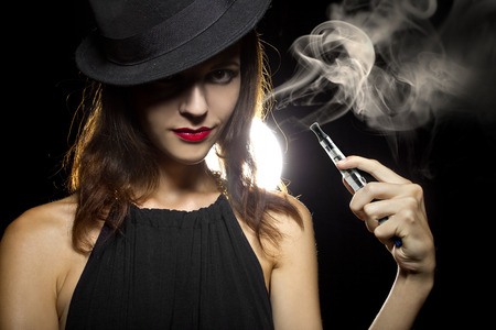 smoke: woman smoking or vaping an electronic cigarette to quit tobacco Stock Photo