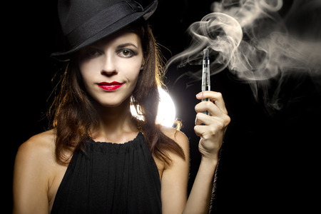 woman smoking or vaping an electronic cigarette to quit tobacco Banco de Imagens