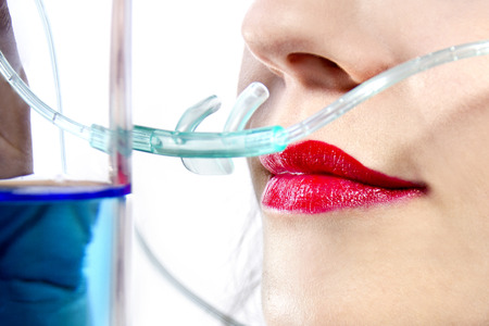 inhaling: woman inhaling flavored oxygen with cannula and scented water Stock Photo