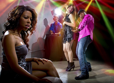 dancing club: black male cheating on girlfriend with seductive white female at club Stock Photo