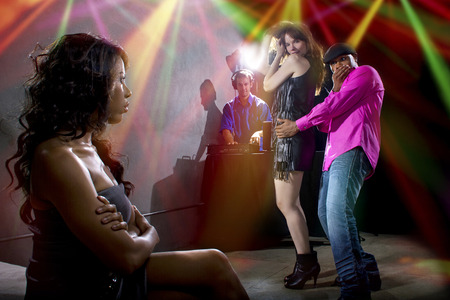 black male cheating on girlfriend with seductive white female at club Banque d'images