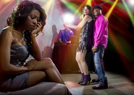 dancing club: single black woman jealous of interracial couple on dancefloor Stock Photo