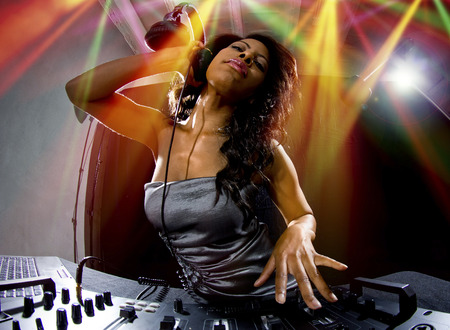 crossfader: young african american female dj playing music at a party Stock Photo