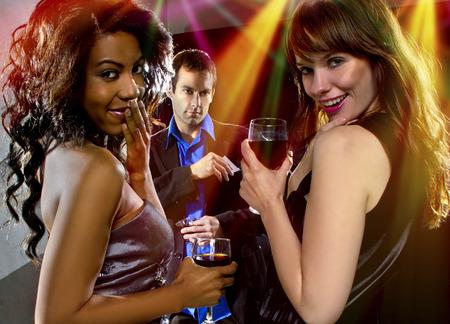 Frauen verführen einen Mann in einer Bar oder Diskothek Standard-Bild - 35702594