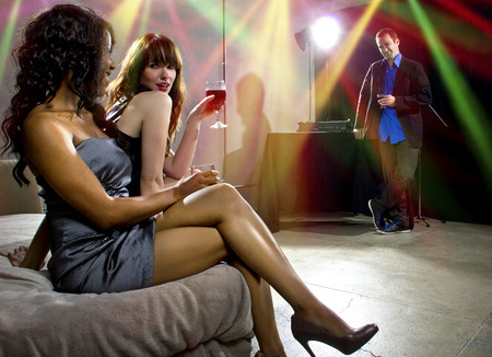 women seducing a man at a bar or nightclub