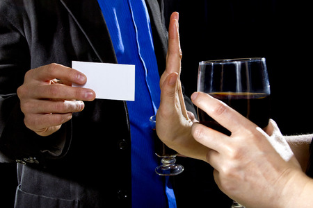businesscard: businessman handing over businesscard to a female at a bar Stock Photo