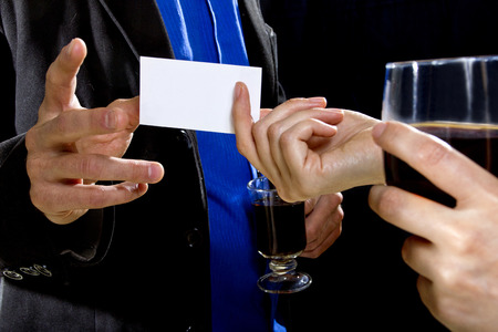 hand business card: businessman handing over businesscard to a female at a bar Stock Photo