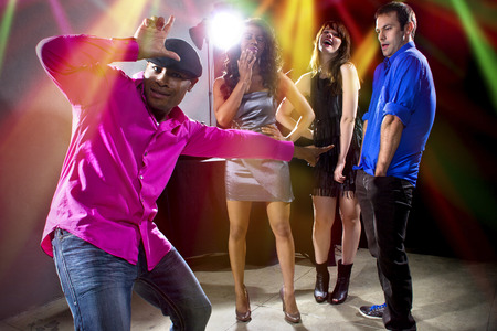 awkwardness: laughing at a man getting rejected by girls at a nightclub Stock Photo