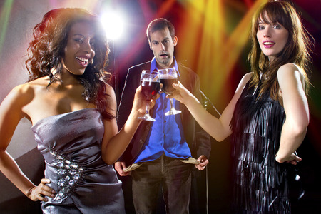 seducing: women seducing a man to buy them cocktails at a nightclub