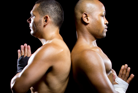 fierce competition: black boxer posing with latino opponent on a black background
